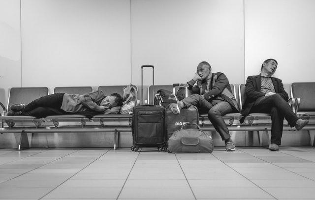 Ľudia spiaci na lavičkách na letisku