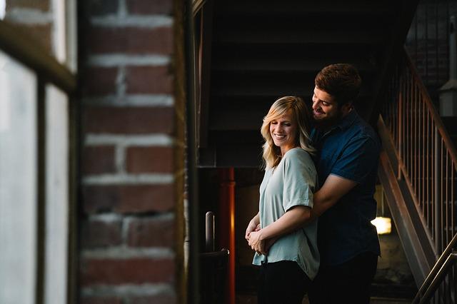 Muž objíma ženu a stoja pri sklenenej stene v dome.jpg