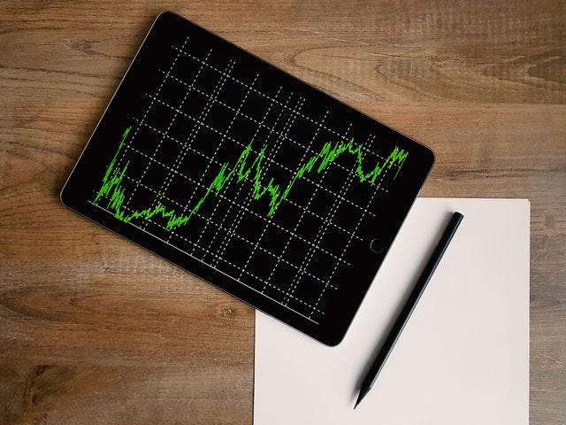 Čierny tablet so zeleným grafom, papier a pero položené vedľa seba na stole