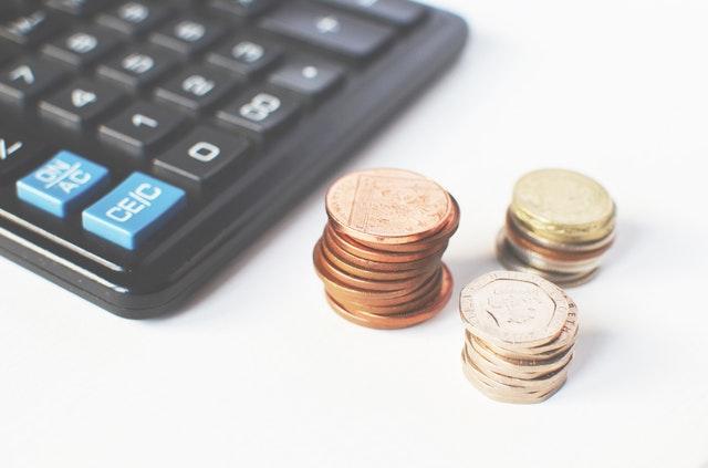 Čierna kalkulačka na bielom stole a mince.jpg